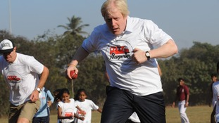 Rugby player Lawrence Dellaglio and Boris Johnson play the 'ball game' with local children involved in a charity project in Mumbai.