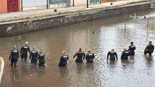 Police search a drained section of canal
