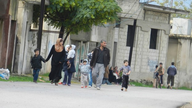 Residents flee their homes due to shelling at Houla, near Homs on November 18