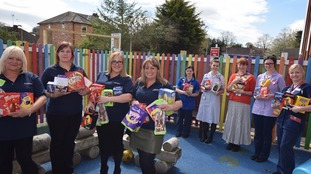 MacGregor Ward staff being presenting armfuls of Easter eggs.