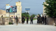 Afghan soldiers stand guard at the gates of the military compound.