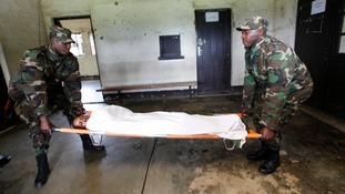 Rwanda army officers carry a wounded FDLR rebel fighter
