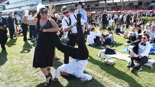 A man tries to do a headstand on Derby Day at Flemington Racecourse.