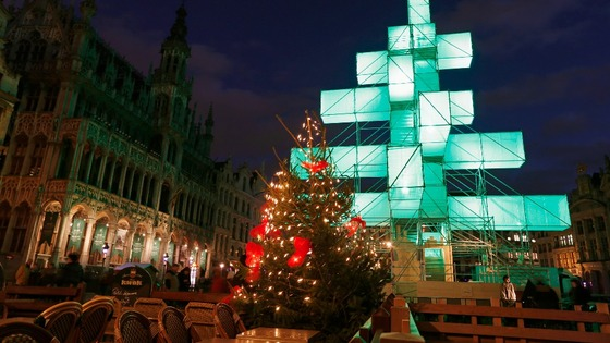A traditional Christmas tree stands at the foot of the illuminated steel installation at Brussels' Grand Place