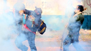 Protesters hurl a gas canister at the police while engulfed in tear gas during protests against Mexico's President Enrique Pena Nieto.
