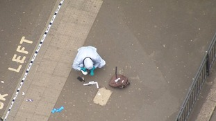 A forensics officer investigates a bag and what appears to be a knife on the pavement.