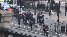 Armed police surround a man on the ground.