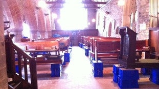 Pews propped up on boxes after flooding affected St Denys Church in Kempsey