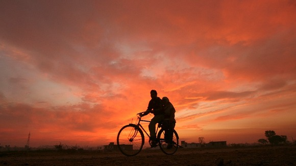 Two people ride a bicycle as the sun sets on the outskirts of Jammu in India.