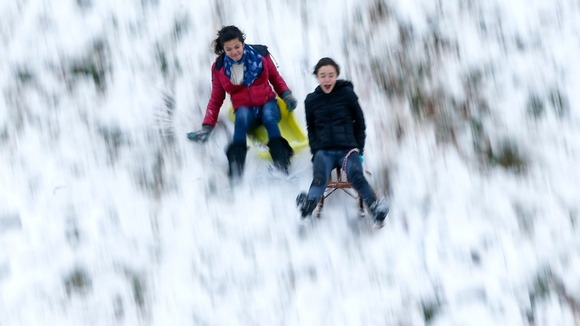 Children ride sledges down an hill as the first snowfall of the season hits Brussels.