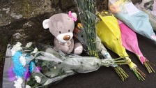 Flowers and a teddy bear have been left on the road where two people lost their lives.