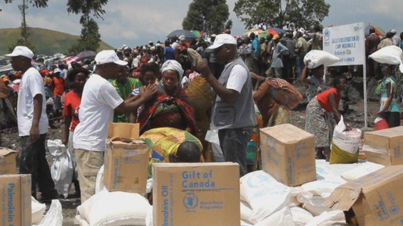 Food aid bags and boxes of oil are given out to those queuing at UN camp