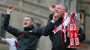 Blades boss Chris Wilder almost drops the trophy during open-top bus parade