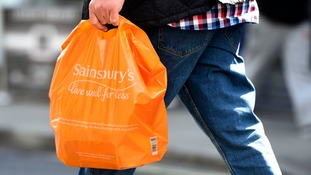 A man carries a Sainsbury's shopping bag.