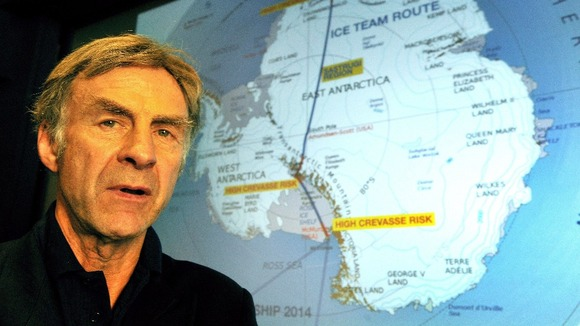 British explorer Sir Ranulph Fiennes stands in front of a projection that shows the route of the Coldest Journey on Earth.