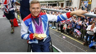 Quadruple gold medal winning Paralympian David Weir shows his medals as he takes part in the parade through London in September