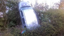 The car ended up vertical in a hedge