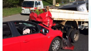 A red Vauxhall Astra crashed into the back of a truck.