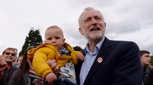 Labour leader Jeremy Corbyn holds one-year-old Angelo after speaking to supporters at a rally in Harlow.