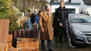 The Prince of Wales walks with flooded home owner Martin Jones