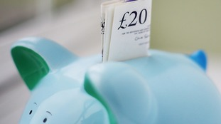 twenty pound note sticking out of a piggy bank