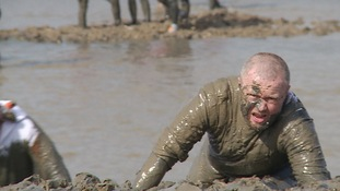 Many of the entrants had to crawl through the mud to complete the course.