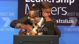 Qantas boss Alan Joyce gets a cream pie in the face during speech