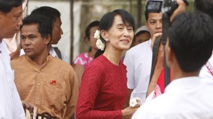 Burma's National League for Democracy party leader Aung San Suu Kyi heads towards a polling station at Wah Thin Kha