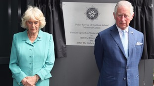 Charles and Camilla unveil a plaque at the memorial garden at the PNSI headquarters.