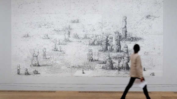 A member of the public walks past a large scale drawing by Paul Noble