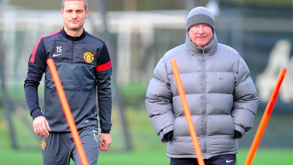 Nemanja Vidic and Sir Alex Ferguson keep warm in training