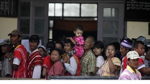 Myanmar villagers line up to cast their vote outside a polling station in Wah Thin Kha, Myanmar