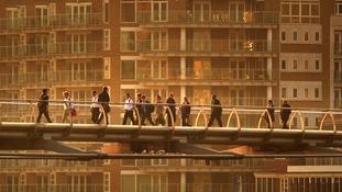 Commuters cross Millennium Bridge at sunrise in London.