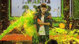 Will Smith hides behind Justine Bieber as he gets slimed at the 2012 Nickelodeon Kid's Choice awards