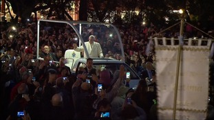 Francis greets followers from a lit-up Popemobile.