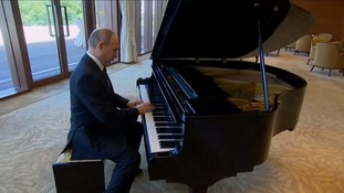 Putin plays the piano as he waits for Chinese president