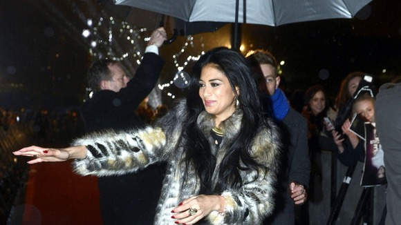 Nicole Scherzinger braves the rain to greet fans