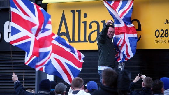Campaigners hand a Union flag from the office of an Alliance MP
