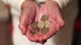 An elderly person holds money.
