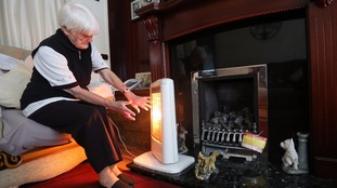 An elderly woman sits by a heater.