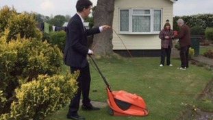 Ed Miliband cuts a lawn on the campaign trail.