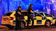 Armed police patrol the area outside Manchester Arena on Monday evening.