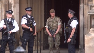 A solider stands guard with armed police.