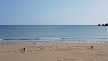 """Two people marking """"pray for Manchester"""" at St. Brelade in Jersey."""