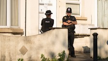 Police guard a residence in Manchester