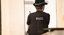 Police Officers guard a house in Manchester as part of the investigation