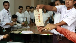 Officials show a ballot paper that shows a vote for Aung San Suu Kyi's National League for Democratic party.
