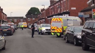 Police at the scene of searches in Rusholme on Sunday.