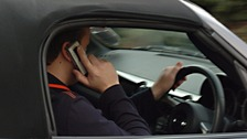 A motorist uses his phone while driving.
