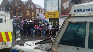 Protesters gather outside the offices of the Alliance Party in Belfast